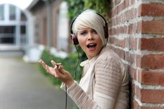 有耳机的美丽的白肤金发的妇女 免版税库存图片