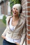 有耳机的美丽的白肤金发的妇女 免版税图库摄影