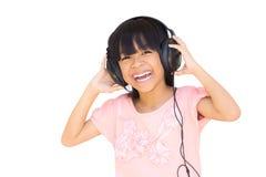 有耳机的美丽的逗人喜爱的愉快的小女孩 免版税库存照片
