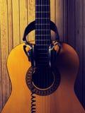 有耳机的老声学吉他 免版税图库摄影