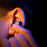 有耳机的耳朵 免版税库存图片