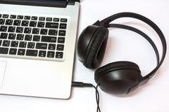 有耳机的膝上型计算机 免版税图库摄影