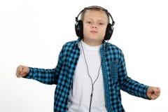 有耳机的英俊的青少年的男孩在顶头listenin 库存照片