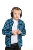 有耳机的英俊的青少年的男孩在头 免版税库存照片