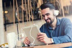 有耳机的英俊的年轻人使用在咖啡店的片剂计算机 免版税库存图片