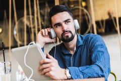 有耳机的英俊的年轻人使用在咖啡店的片剂计算机 库存照片