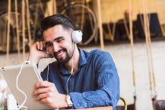 有耳机的英俊的年轻人使用在咖啡店的片剂计算机 免版税库存照片