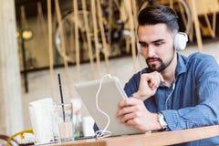有耳机的英俊的年轻人使用在咖啡店的片剂计算机 图库摄影