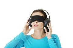 有耳机的蒙住眼睛的可爱的妇女 库存照片