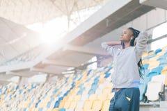 有耳机的观看在体育场的严肃的美国黑人的女孩的特写镜头边画象比赛 免版税图库摄影