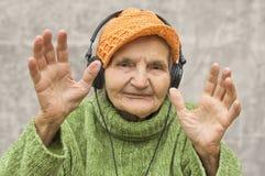 有耳机的资深妇女听到音乐的 免版税库存照片