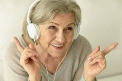 有耳机的资深妇女 免版税库存照片