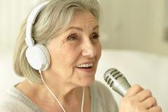 有耳机的资深歌手妇女 库存图片