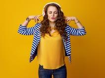 有耳机的轻松的时髦的妇女听到音乐的 免版税图库摄影