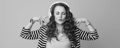 有耳机的轻松的时髦的妇女听到音乐的 库存照片