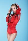 有耳机的迷人的妇女DJ听到音乐的 免版税库存图片