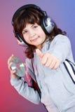 有耳机的逗人喜爱的女孩 免版税库存图片
