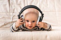有耳机的逗人喜爱的婴孩在家听到音乐 免版税库存图片