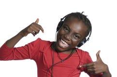 有耳机的非洲女孩听到音乐的 免版税库存图片