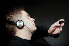有耳机的年轻人使用mp3音乐播放器 免版税库存照片