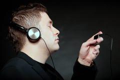 有耳机的年轻人使用mp3音乐播放器 免版税库存图片