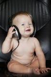 有耳机的婴孩在扶手椅子 库存图片