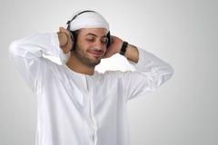 有耳机的年轻愉快的阿拉伯人听到音乐的 免版税库存图片