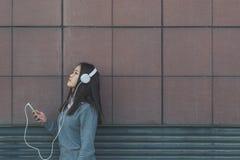 有耳机的年轻美丽的中国女孩 免版税库存照片
