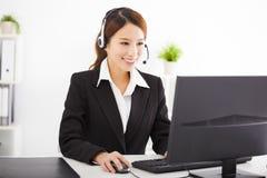 有耳机的年轻美丽的女实业家在办公室 免版税图库摄影