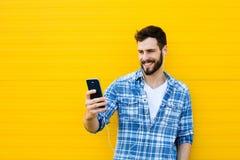 有耳机的年轻英俊的人在黄色墙壁上 库存图片