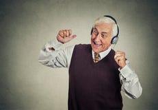 有耳机的年长人听到收音机的享受音乐 免版税库存图片