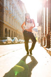有耳机的Hip Hop女孩在一个城市环境里 库存图片