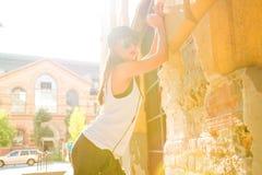 有耳机的Hip Hop女孩在一个城市环境里 库存照片