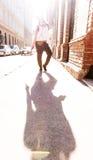 有耳机的Hip Hop女孩在一个城市环境里 免版税库存图片