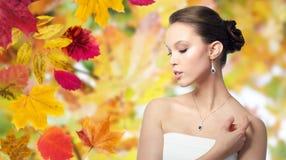 有耳环和垂饰的美丽的亚裔妇女 免版税库存照片