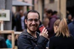 有耳环微笑的年轻男孩,当喝在街道上时的一份咖啡 免版税库存照片