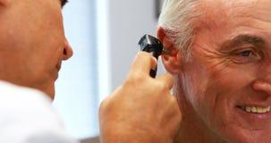 有耳镜的医生审查的患者耳朵 股票视频