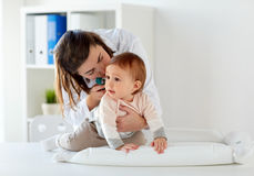 有耳镜的医生检查婴孩耳朵的在诊所 库存照片