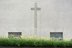 有耶稣受难象十字架和黄色花的教会墙壁 免版税库存照片