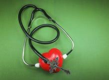 有耶稣受难象和吸水的红色心脏的医疗听诊器 免版税库存图片
