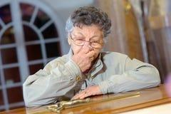 有耶稣受难象的年长妇女 免版税库存照片