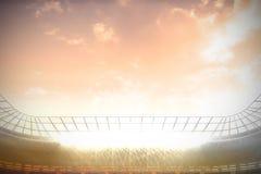 有聚光灯的大橄榄球场在桃红色天空下 库存图片
