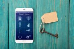 有聪明的家的app智能手机在木书桌上 图库摄影
