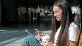 有聪明的电话和咖啡的年轻美丽的学生女孩在商城 免版税库存图片