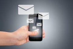 有聪明的电话和电子邮件象的手 免版税库存图片