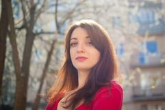 有肉欲的嘴唇的年轻深色的妇女在红色衬衣享用春天微风的户外,当太阳发光时 库存照片
