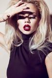 有肉欲的嘴唇的美丽的性感的白肤金发的女孩,时尚头发,黑礼服 秀丽表面 免版税库存图片