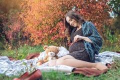 有肚子的妊妇坐毯子并且讲故事给婴孩 怀孕和秋天和谐的概念 免版税库存照片