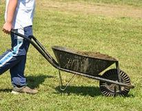有肥料的人在独轮车 免版税库存图片