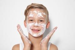 有肥皂泡沫的逗人喜爱的小男孩在面孔 免版税库存照片